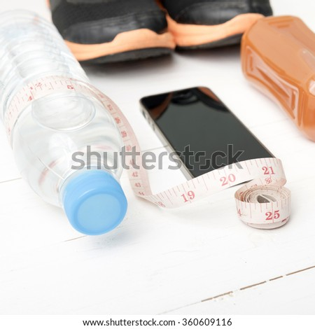 fitness equipment:running shoes,measuring tape,water,juice and phone on white wood background