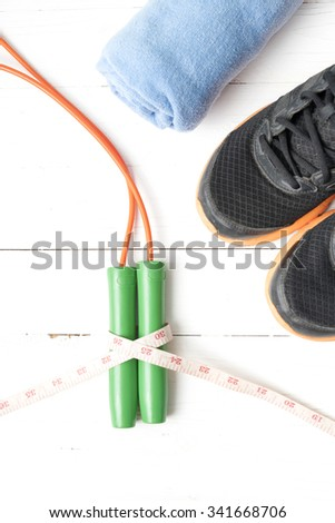 fitness equipment : running shoes,towel,jumping rope and measuring tape on white wood table