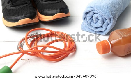fitness equipment : running shoes,towel,jumping rope and orange juice on white wood background