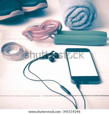 fitness equipment : running shoes,towel,jumping rope,phone and measuring tape on white wood table vintage style