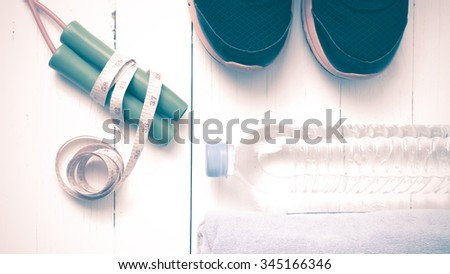 fitness equipment : running shoes,towel,jumping rope,water bottle and measuring tape on white wood table vintage style