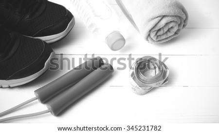 fitness equipment : running shoes,towel,jumping rope,water bottle and measuring tape on white wood table black and white color tone style