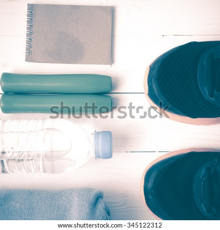 fitness equipment : running shoes,towel,jumping rope,water bottle and notepad on white wood table vintage style