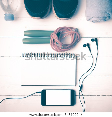 fitness equipment : running shoes,towel,jumping rope,water bottle,phone and notepad on white wood table vintage style