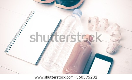 fitness equipment:running shoes,water,measuring tape,notepad,phone and juice on white wood background vintage style