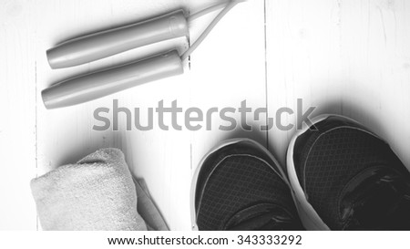 fitness equipment: towel,jumping rope and running shoes on white wood table black and white color style