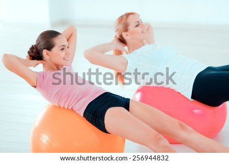 Fitness every day. Closeup side view image of beautiful teenage girl and her mother in sports clothing training on fitness balls in sports club  - stock photo