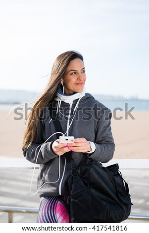 Fitness female athlete using her smartphone. Sporty urban woman in pink pattern leggings listening music. - stock photo
