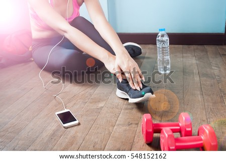 Fitness female in black pants and sneaker stretching after workout with copy space
