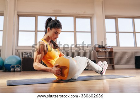 Fitness female model exercising with kettle bell weight at the gym. Fit young woman doing workout at health club. - stock photo