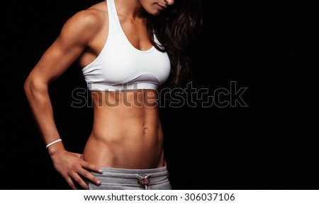 Fitness female model torso with her hands on hips. Female with perfect abdomen muscles standing against black background. Cropped shot with copyspace. - stock photo