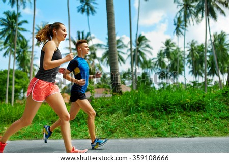 Fitness. Fit Athletic Couple Running On Road, Training For Marathon. Sporty Runners Jogging During Outdoor Workout. Joggers Training. Sports. Healthy Lifestyle And Wellness. Health Conscious Concept - stock photo