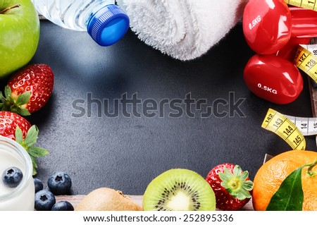 Fitness frame with dumbbells, towel and fresh fruits. Copy space