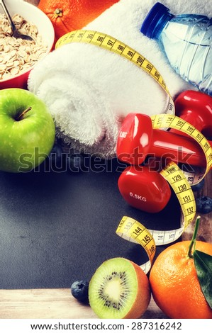 Fitness frame with dumbbells, water bottle and fresh fruits. Healthy lifestyle concept with copy space - stock photo