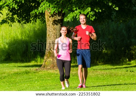 Fitness Friends running together through park - stock photo