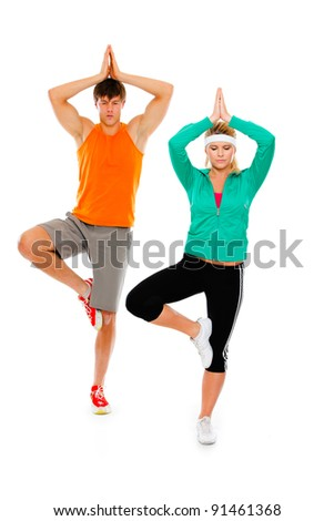 Fitness girl and man in sportswear doing yoga isolated on white - stock photo