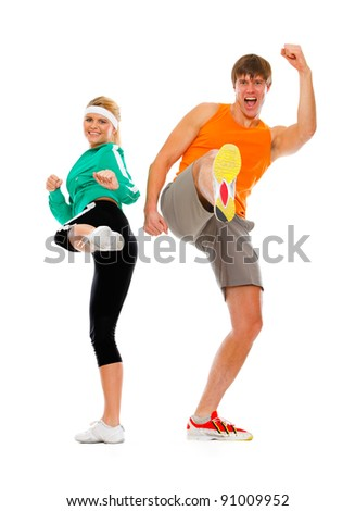 Fitness girl and man in sportswear kicking isolated on white