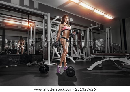 fitness girl doing exercise with dumbbells in the gym - stock photo