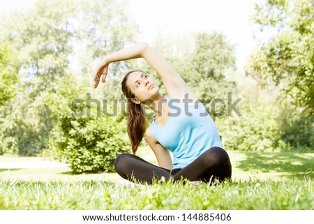 Fitness girl doing stretching exercise outdoor.