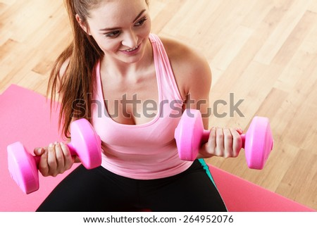 Fitness girl fit woman with dumbbells, doing exercise with dumb bells training with weights at home - stock photo