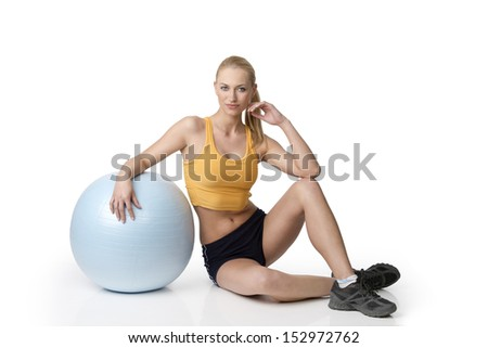 fitness girl in gym dress sitting on white with a ball near her . natural skin - stock photo