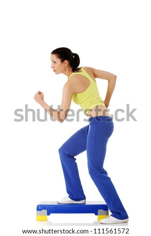 Fitness girl is working out with stepper , isolated on white background - stock photo