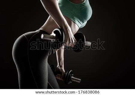 Fitness girl lifting dumbbells on black background - stock photo