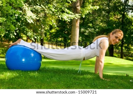 Fitness girl outdoor exercise by pilates ball.