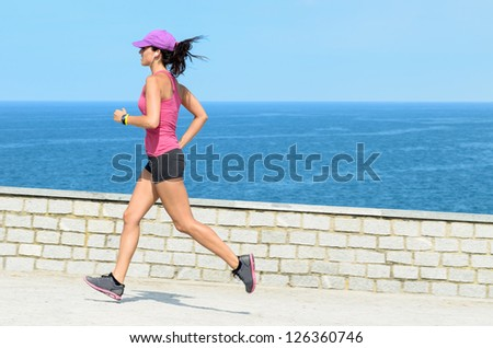 Fitness girl running fast on summer day with sea on background. Beautiful female athlete exercising wearing sport cap.