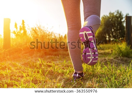 Fitness Girl running in a field with colorful outfit - stock photo