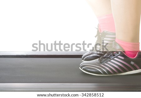 Fitness girl running on treadmill. Woman with muscular legs on white background - stock photo