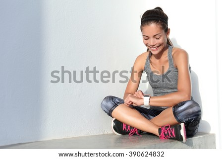 Fitness girl using activity tracker smartwatch as heart rate monitor for workout or tracking her weight loss improvement. Woman runner living a healthy life. Wearable tech. - stock photo