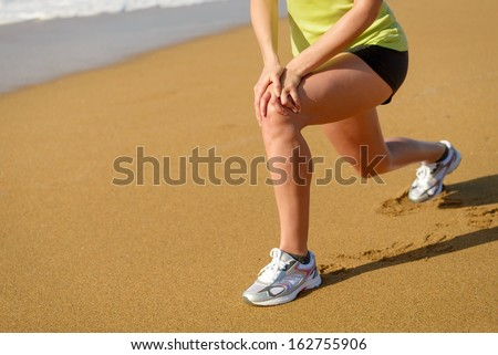 Fitness girl warming up and stretching before running in beach. Woman with running knee injury.