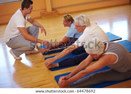 Fitness group stretching in a gym with trainer - stock photo