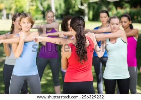 Fitness group warming up in park on a sunny day - stock photo