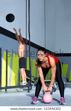 Fitness gym Kettlebell woman and jumping wall ball man  workout at gym - stock photo