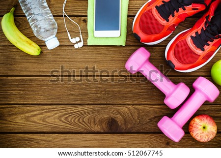 Fitness, healthy and active lifestyles Concept, dumbbells, sport shoes, bottle of waters, smartphone with headphone, banana and apples on wood background. copy space for text. Top view