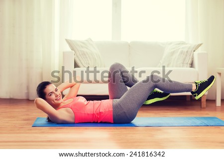 fitness, home and diet concept - smiling teenage girl doing exercise on floor at home - stock photo