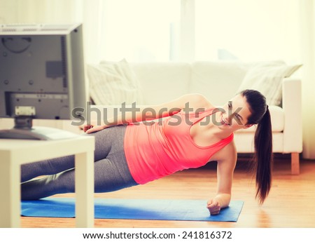 fitness, home and diet concept - smiling teenage girl doing side plank and watching tv at home - stock photo