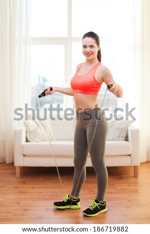 fitness, home and diet concept - smiling teenage girl with skipping rope at home - stock photo