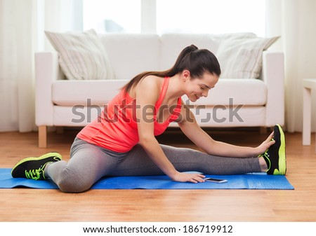 fitness, home, technology and diet concept - smiling teenage girl streching on floor with smartphone at home - stock photo