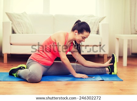fitness, home, technology and diet concept - smiling teenage girl streching on floor with smartphone and earphones at home - stock photo