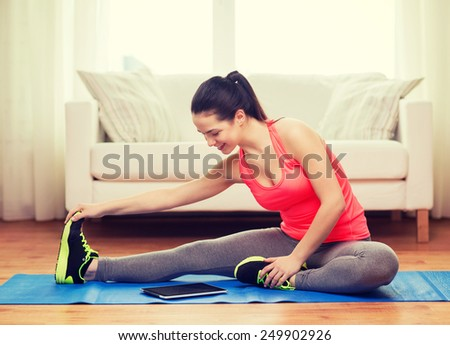 fitness, home, technology and diet concept - smiling teenage girl streching on floor with tablet pc computer at home - stock photo