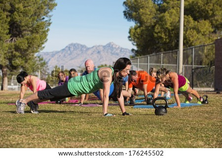 Fitness instructor leading group in push up exercises outdoors - stock photo