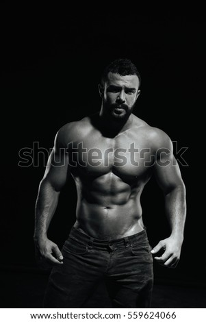 Fitness male model standing on black background