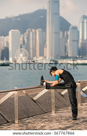 Fitness man doing stretching along Hong Kong promenade. Filtered image.