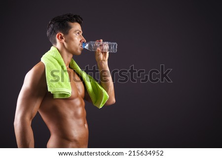 Fitness man drinking a bottle of fresh water on black background - stock photo