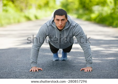 Fitness man exercising push ups, outdoor. Muscular male cross-training on city park - stock photo