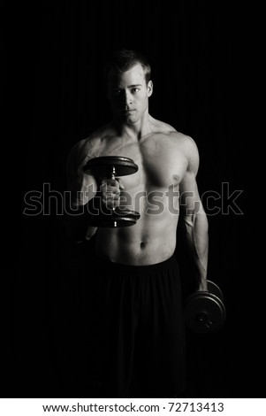 Fitness man lifting weights, low key - stock photo