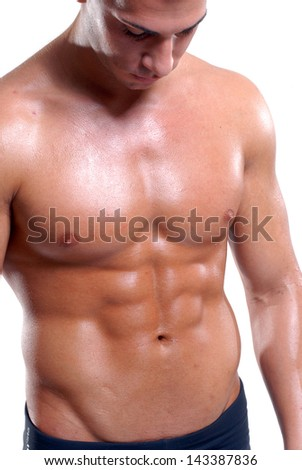 Fitness man looking his abdominal muscle. - stock photo